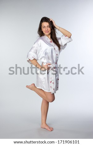 Young beautiful brunette in peignoir isolated on white background