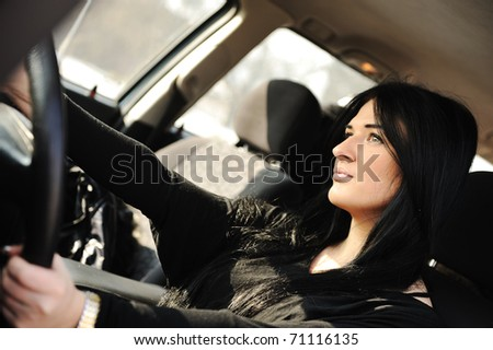 Young beautiful brunette inside the car with wheel in hands - stock photo