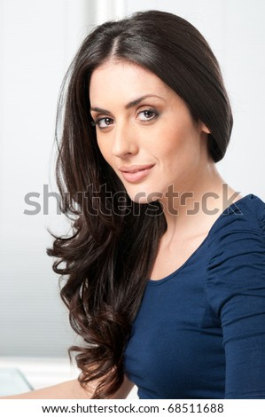 Young beautiful brunette lady smiling and looking at camera - stock photo