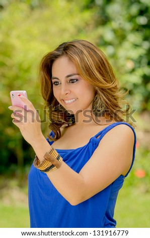 Young beautiful brunette lady touching and browsing her smart phone at the park