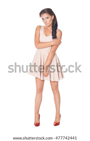Young beautiful brunette posing in a beige dress on a white background