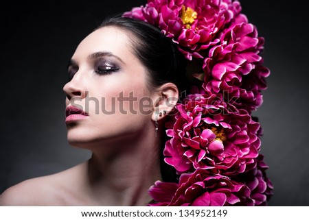 Young beautiful brunette posing with flowers on her head