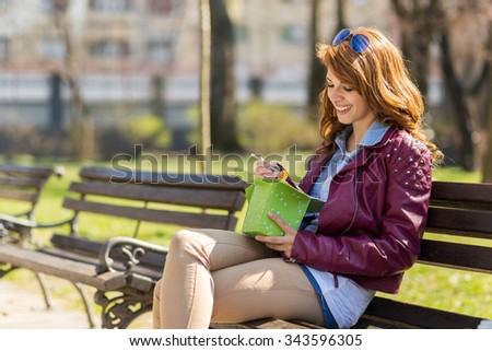 Young, beautiful brunette sitting on a wooden bench in a park on a sunny day eating Chinese food