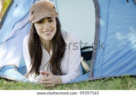 Young beautiful brunette smiling outside of a tent on a camping trip