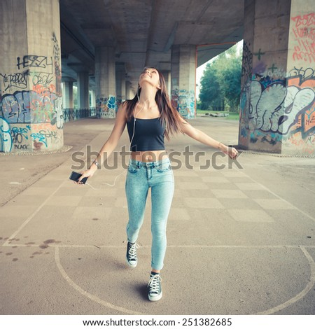 young beautiful brunette straight hair woman listening music outdoor - stock photo