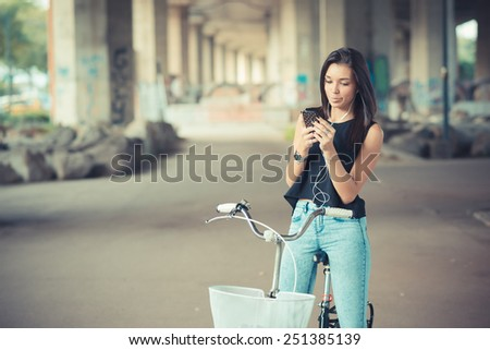 young beautiful brunette straight hair woman using bike and smartphone listening music outdoor - stock photo
