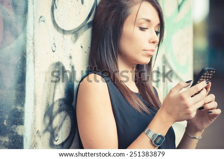 young beautiful brunette straight hair woman using smartphone outdoor - stock photo