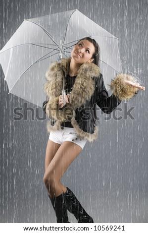 young beautiful brunette under a umbrella checking rain - stock photo