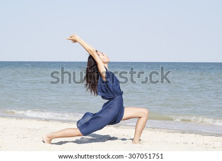 Young beautiful brunette woman doing yoga at seaside in blue dress