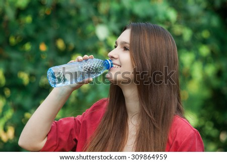 young beautiful brunette woman drinking a water from bottle in a park.Young woman drinking water at workout, outdoors - stock photo