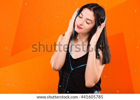 Young beautiful brunette woman, in black blouse, listening to music with big headphones on geometric orange background with blue and white dots - stock photo