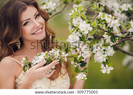Young beautiful brunette woman in blooming garden. Bride.beautiful cute tender young blonde girl in a garden of flowering trees. Beautiful bride in wedding dress posing in a blooming apple garden.  - stock photo