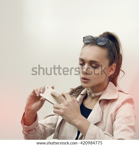 Young beautiful brunette woman in casual style clothes talking on her phone and making selfie with her mobile camera. Portrait of attractive fashion looking girl model. Hipster.