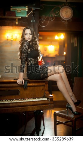 Young beautiful brunette woman in elegant black dress sitting provocatively on vintage piano. Sensual romantic lady with long dark hair in luxurious interior, daydreaming. Attractive girl posing   - stock photo