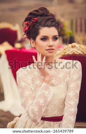 Young beautiful brunette woman in elegant lace dress sitting in garden. fashion portrait - stock photo
