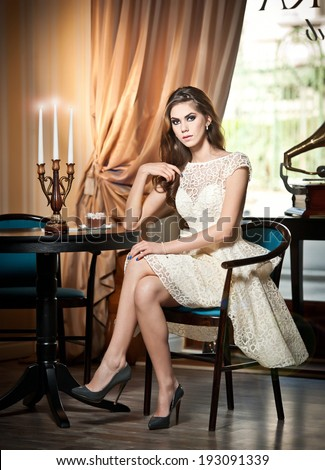 Young beautiful brunette woman in elegant lace dress sitting near a table with candlestick. Long hair attractive girl in luxurious classic interior. Seductive female in vintage scenery, indoor - stock photo