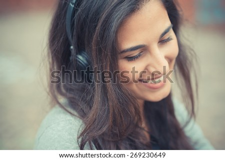 young beautiful brunette woman listening music with headphones in the city