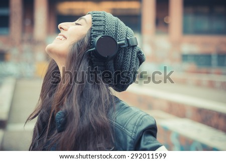 young beautiful brunette woman listening music with headphones in the city - stock photo