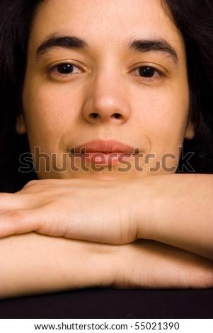 young beautiful brunette woman portrait against black background - stock photo