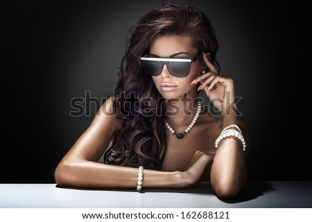 Young beautiful brunette woman posing wearing sunglasses and jewelry. - stock photo