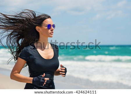 Young beautiful brunette woman running outdoors on the beach. Close up portrait. Miami, Florida.