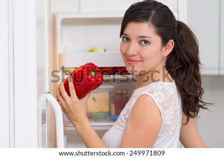 young beautiful brunette woman searching for food in the fridge holding red pepper - stock photo