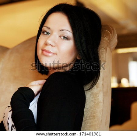 young beautiful brunette woman sit in chair - stock photo