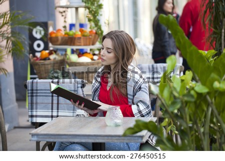 Young beautiful brunette woman sitting on the street with the restaurant menu - stock photo