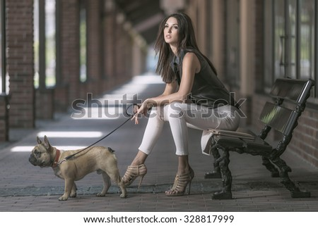 Young beautiful brunette woman sitting with dog on retro bench - stock photo