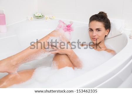 young beautiful brunette woman takes bubble bath - stock photo