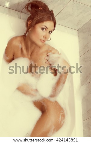 Young beautiful brunette woman takes bubble bath. Concept of care of body. Vintage style - stock photo