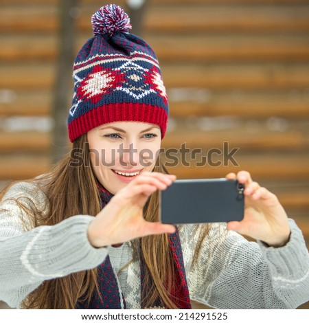 Young beautiful brunette woman using her smart phone over wooden background. focus on face - stock photo