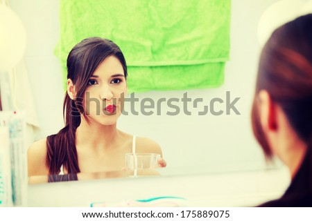 Young beautiful brunette woman using mouthwash at her bathroom - stock photo
