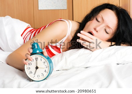 young beautiful brunette woman waking up, switching off the alarm-clock and yawning in the morning - stock photo