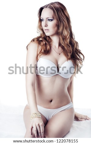 young beautiful brunette woman wearing sexy lingerie sitting at studio on white background