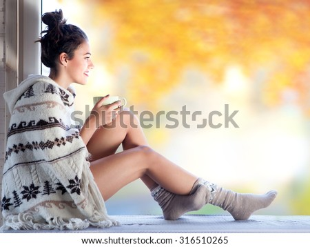 Young beautiful  brunette woman with cup of coffee wearing knitted nordic print poncho sitting home by the window. Blurred  garden fall background.  - stock photo