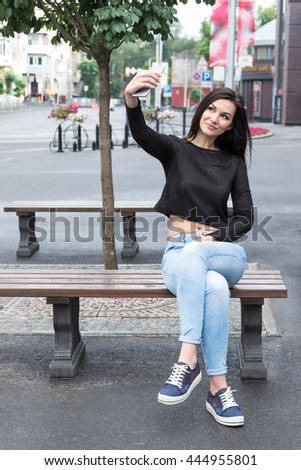 Young beautiful brunette woman with long hair sitting on a bench in the city makes selfie her smartphone - stock photo