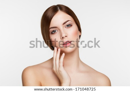 Young beautiful brunette woman with natural makeup on grey background - stock photo