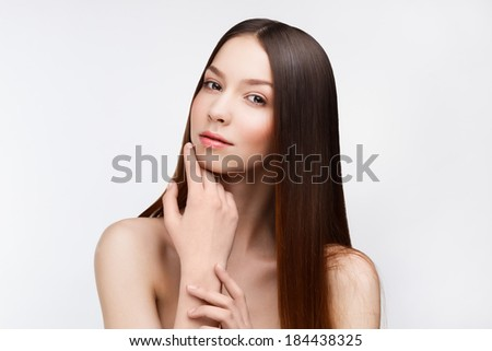 Young beautiful brunette woman with natural makeup on grey background