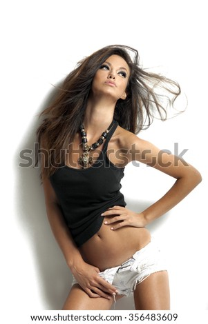 Young beautiful brunette woman with perfect body posing on white background