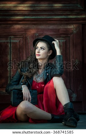 Young beautiful brunette woman with red short dress and black hat posing sensual in vintage scenery. Romantic mysterious young lady relaxing sitting on floor against vintage wooden wall  - stock photo