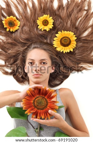 Young beautiful brunette woman with scattered long hairs and sunflower on white