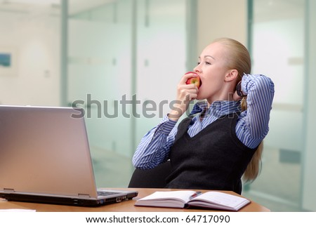 Young beautiful business lady at table resting and eating an apple - stock photo