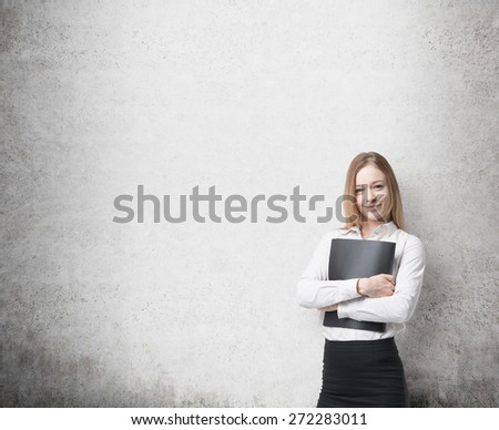 Young beautiful business lady is holding a black document case. A concept of legal services. Concrete background. - stock photo