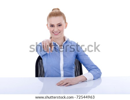 Young beautiful business woman behind the desk pointing at you, isolated - stock photo
