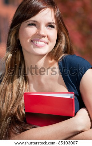 Young beautiful business woman hoding diary at city park. Student - stock photo
