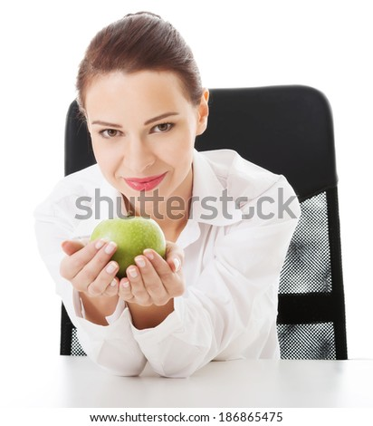 Young beautiful business woman holding an apple. Isolated on white.