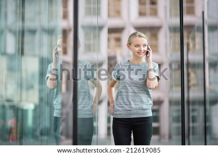 Young beautiful business woman in modern glass interior speaking on the phone