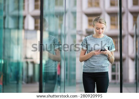 Young beautiful business woman in modern glass interior using the phone - stock photo