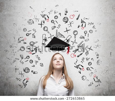 Young beautiful business woman is thinking about education at business school. Drawn business icons over the concrete wall. Graduation hat. - stock photo